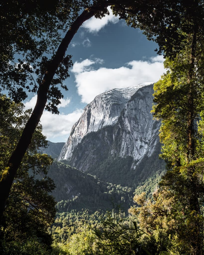 A mountain surrounded by trees that create a frame for the image